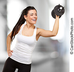 portrait of young girl training with weights indoor