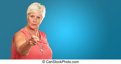 Portrait Of A Senior Woman Pointing Finger On Blue...