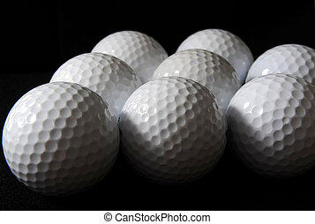 Golf balls - many golf balls on the black background