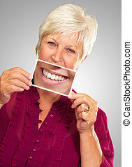 Senior Woman With Manifying Glass Showing Teeth On Gray...