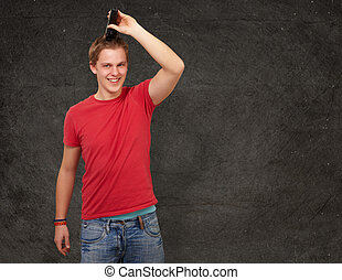 portrait of young man cutting his hair against a grunge wall...