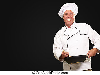 Male Chef Stirring A Non Stick Pan On A Black Background