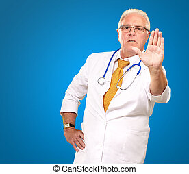 Portrait Of A Male Doctor Showing Warning Sign