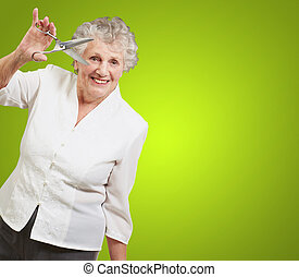Senior woman holding scissors isolated on green background