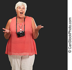 Senior Woman Wearing Camera Shrugging Isolated On Black...