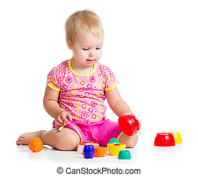 smiling child girl playing with cup toys, isolated over white
