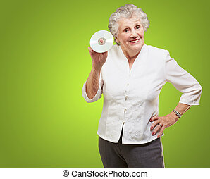 Senior woman holding cd isolated on green background