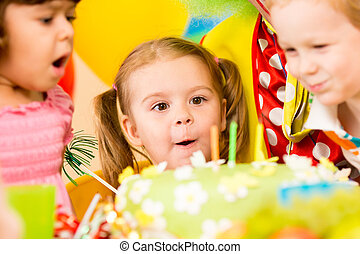 kids celebrating birthday party and blowing candles on cake...