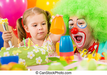child girl playing with clown on birthday party