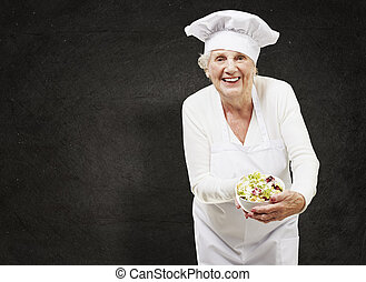 senior woman cook holding a bowl with salad against a grunge...