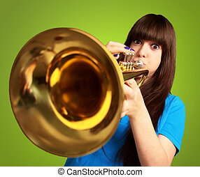 portrait of a young girl blowing trumpet on green background