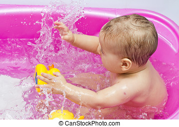 baby bath - Adorable baby having fun while bath time,...