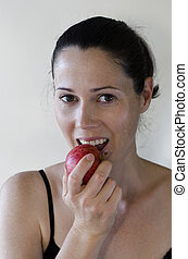 Young woman eats apple on white background