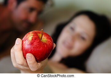 Man and Woman hold Apple in Bed - A man and a young...