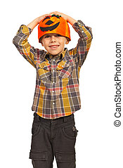 Cheerful boy with pumpkin hat holding hands on head isolated...