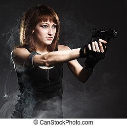 Sexy woman holding gun with smoke