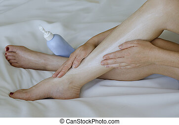 Young woman moisturisers her legs on white background - A...