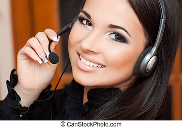 operator - beautiful girl with a headset looking at the...