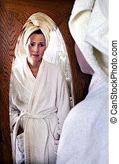 Young Woman looks at herself in the Mirror - A young...
