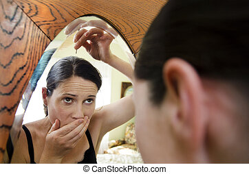 Woman Going Gray - Young caucasian woman looks in the mirror...