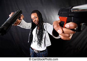 young afro-american woman with gun against black background