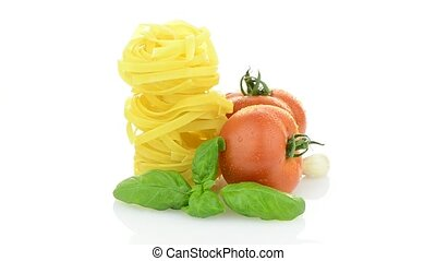 Cherry tomatoes, garlic and pasta rotating Isolated on white...