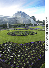Kew Palm House - Well-tended beds of flowers in front of the...