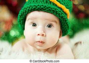 beautiful baby in green knitting hat closeup portrait