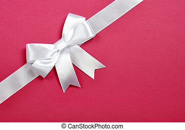 White ribbon whith bow on a pink background