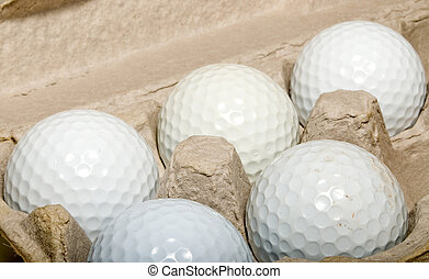 Golf Eggs - Several golf balls in an egg carton.