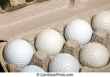 Golf Eggs - Several golf balls in an egg carton