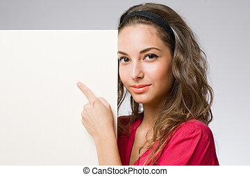 Young brunette pointing at banner. - Portrait of a cute...