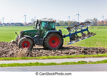 Tractor with plowes on the spring field.