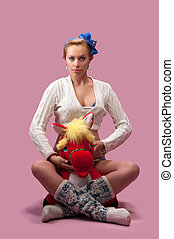 young pregnant woman sitting on the floor with a soft toy...