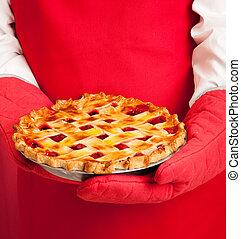 Lattice Top Homemade Cherry Pie - Closeup of a baker's hands...