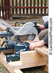 Carpenter sawing plank - Carpenter sawing board with an...