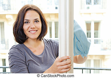 Woman cleaning windowpane - Young smiling woman cleans the...