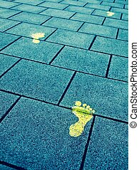 Big steps forward - Yellow paint footprints on sidewalk...