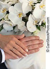 Hands with wedding rings and bouquet  from white orchid