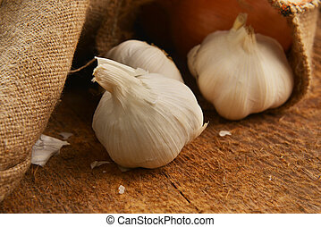 ripe garlic - Open jute sack with ripe garlic on wooden...