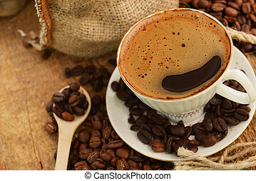 Coffee beans and cup - Roasted coffee beans with cup on jute...