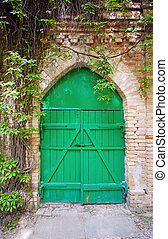 Old green wooden gate in the rural brick wall