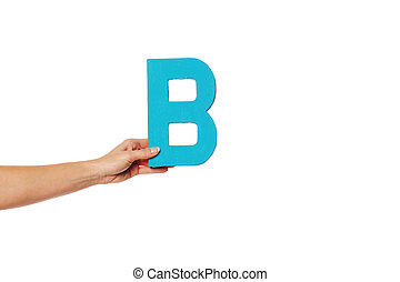 hand holding up the letter B from the left - Female hand...
