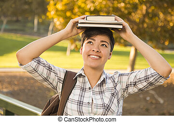 Mixed Race Female Student Holding Books on Her Head