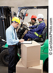 Supervisor With Foremen Working At Warehouse