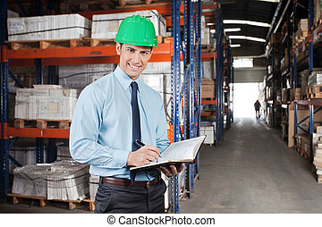 Confident Supervisor With Book At Warehouse - Portrait of...