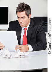 Businessman Reading Document In Office - Young businessman...
