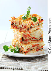 Lasagne - Three portions of lasagne stacked on a plate