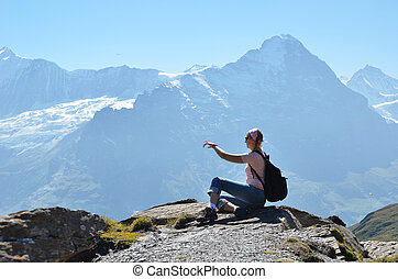 Traveler on the top of a rock Jungfrau region, Switzerland