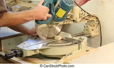 sliding miter saw cutting a cabinet board